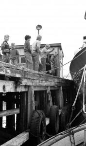 Barn ser på båten Ankenes av Bugøynes som ligger ved kai i Vadsø for frakt av varer.