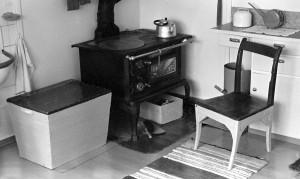 Stol, vedkasse og vedovn i kjøkkenet hos Eilert Randa.