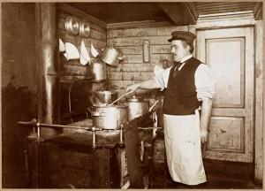 """Lindstrøm (antakelig i 20-åra) står i byssa og lager mat. Bildet er sannsynligvis tatt om bord i """"D/S Hålogaland"""". Fotograf / Photographer: Narve Skarpmoen (1868-1930) Eier / Owner Institution: Nasjonalbiblioteket / National Library of Norway"""