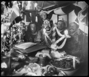 Julefeiring i Gjøahavn 1903 Motiv / Motif: Rundt bordet som er fullt av mat sitter Helmer Hanssen, Roald Amundsen, Adolf Lindstrøm, Gustav Wiik og Anton Lund. Bak står Peder Ristvedt. Dato / Date: 1903 Fotograf / Photographer: Godfred Hansen (1876-1937) KUVA NASJONALBIBLIOTEKET