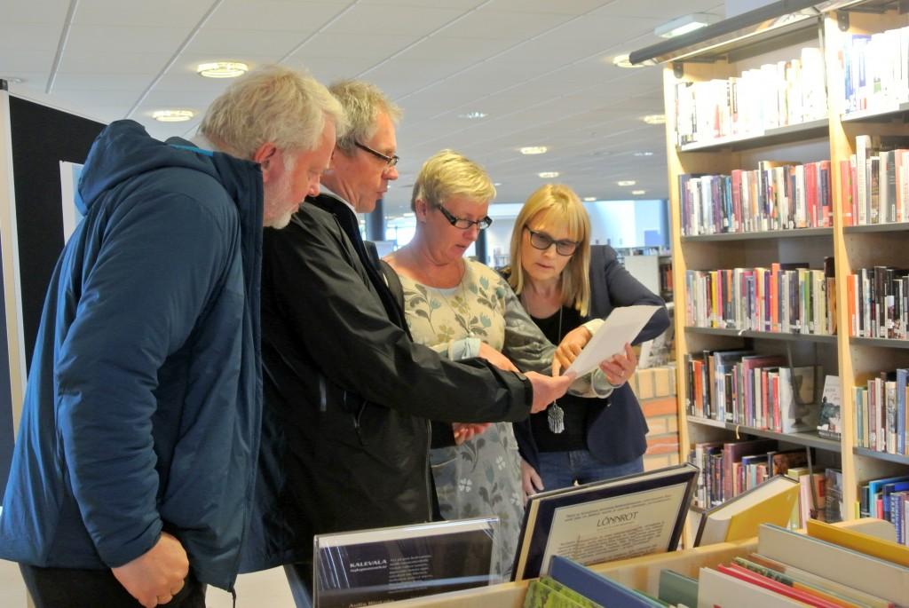 Riksantikvar Jørn Holme, Finlands ambassadør Erik Lundgren og hans kone fikk se på gamle finske dokumenter på biblioteket i Vadsø. KUVA HEIDI NILIMA MONSEN