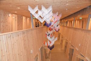 Outi Pieskis installasjon av trådrysjer og metallstenger henger ned som en «uro» fra overlystaket, der de bevegelige tekstilene bringer noe levende og taktilt inn i bygget. Med en stram henvisning til den samiske folkedraktens sjal, nærmere bestemt sjalets v-form, dannes det henholdsvis opake og transparente mønster som forandres ettersom hvor en er i bygget. KUVA ANNE RASMUS, AVVIR