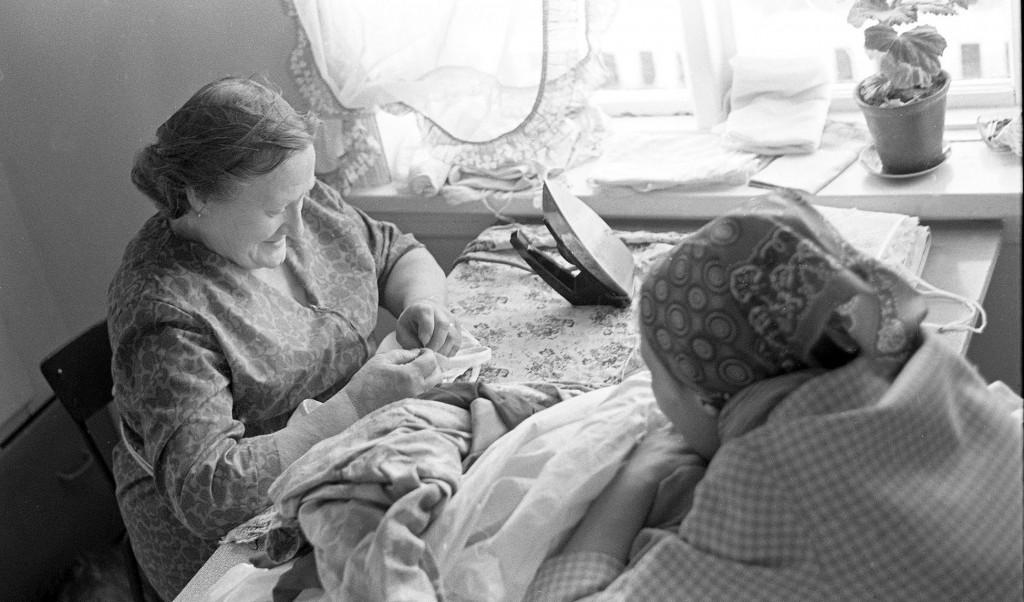 To kvinner stryker klær ved kjøkkenvinduet. KUVAT: VENKE OLSEN, Tromsø Museum – Universitetsmuseet