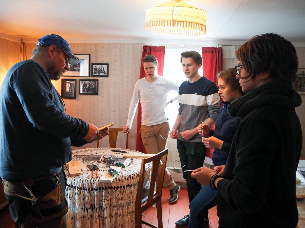 Museumshåndverker Johnny Sommer viser elevene hvordan man tvinner ståltråden for å lage en visp. KUVAT KAISA MALINIEMI