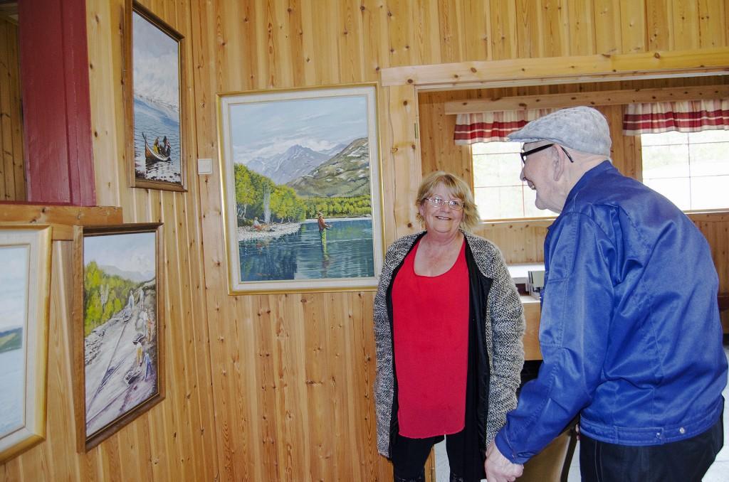 Leif Johannessen, her sammen med Anne-Gerd Jonassen, studerer bildene til den lokale kunstneren Helge Mikalsen nøye. Spesielt maleriet som viser et gjeng arbeidskarer som driver veibygging, får Johannessens minner til å flomme. KUVA HEIDI NILIMA MONSEN