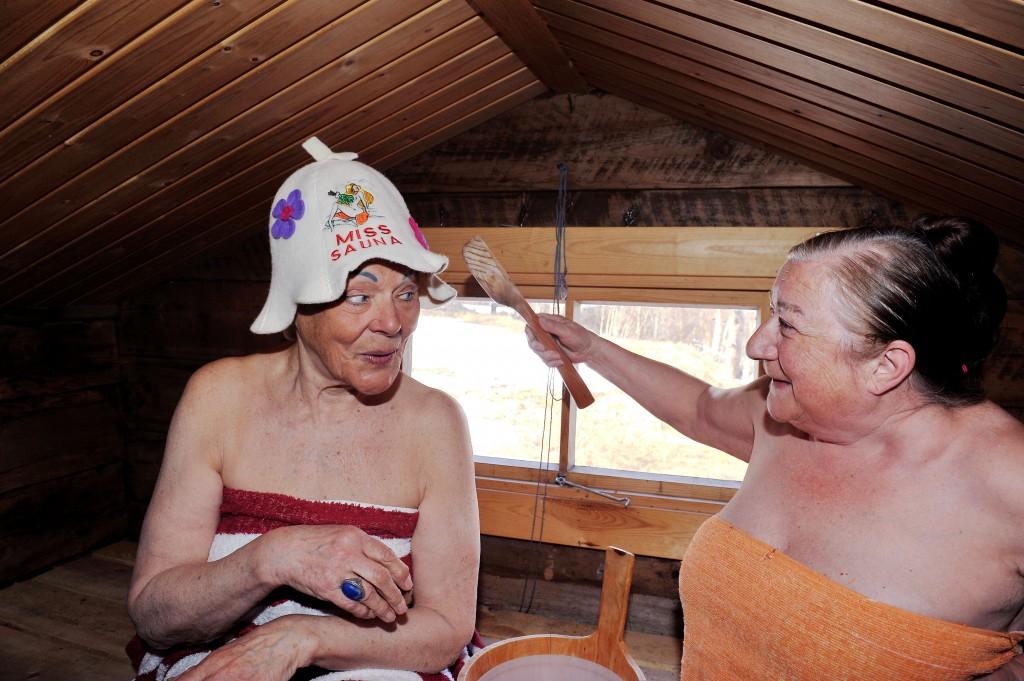 Tässä oon kaksi «Miss Saunaa», mutta tyhä toisela oon saunamyssy. • Her er to Miss Sauna, men bare én har badstuhatt.